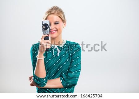 Beautiful retro woman holding old fashioned video camera,Recording moments - stock photo