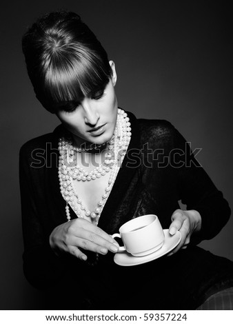 Beautiful retro woman with red lips holding cup of coffee. black and white picture - stock photo