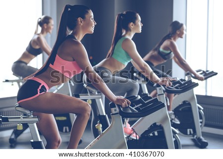 Beautiful ride. Side view of young beautiful women with perfect bodies in sportswear looking away with smile while cycling at gym - stock photo