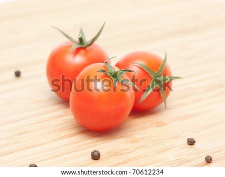 Beautiful ripe cherry tomatoes isolated on cutting board