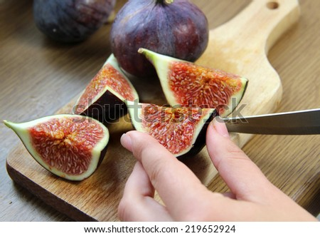 Beautiful ripe fresh pulpy figs on the wooden table - stock photo