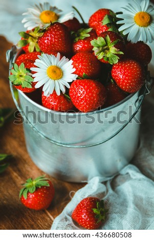 Beautiful ripe strawberry in bucket with daisies - stock photo