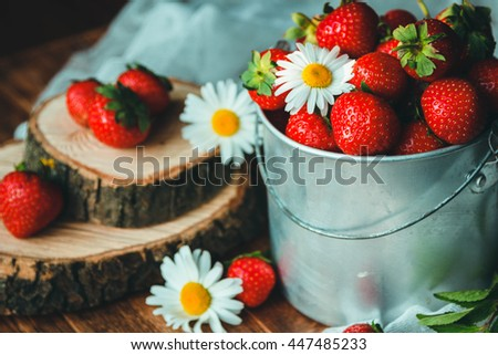 Beautiful ripe strawberry in bucket with daisies
