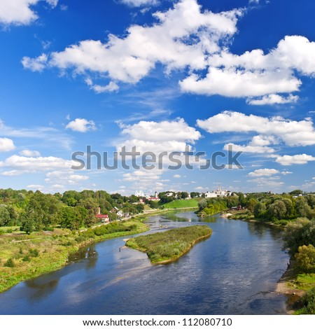 Beautiful river landscape with an island and a cloudy sky - stock photo
