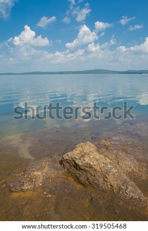 Beautiful river landscape with stones on blue sky background