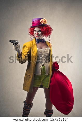 beautiful robber clown with gun and big sack of money - stock photo