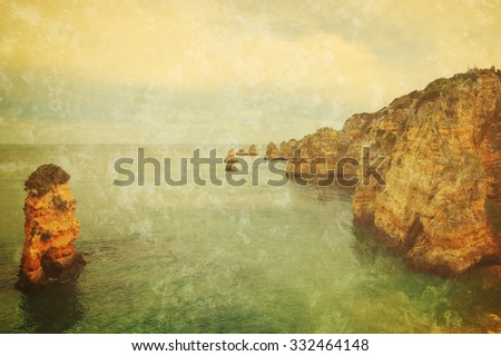 Beautiful rock formations, stone arches and caves at Dona Ana Beach and sailing boats on horizon (Lagos, Algarve coast, Portugal) in the evening light. Retro aged photo with scratches. - stock photo