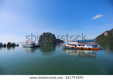 Beautiful rocks mountain and crystal clear sea,Adventure landscape background. Wooden fishing boat on sea coast of tropical island in Thailand at sunny day of summer vacations in Asia - stock photo