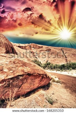 Beautiful rocks of Australian Outback against colourful sky. - stock photo