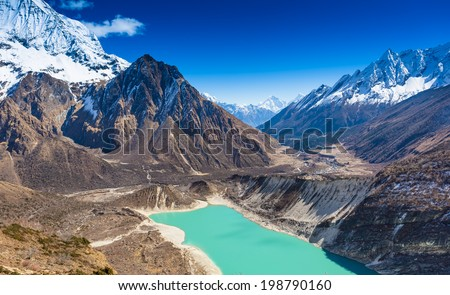 Beautiful rocky and snow capped mountains with lake against the blue sky. Himalaya, Nepal - stock photo