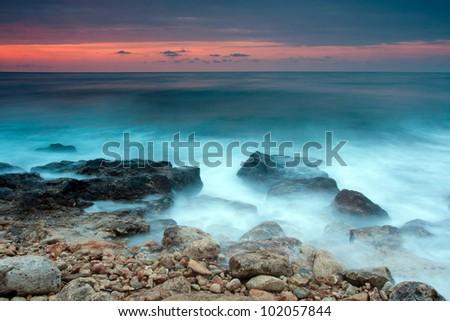 Beautiful rocky sea beach at the sunset - stock photo