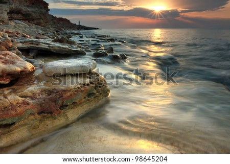Beautiful rocky sea beach at the sunset in the summer