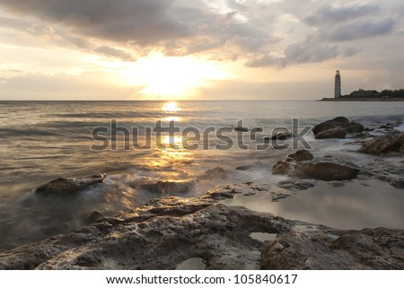 Beautiful rocky sea beach at the sunset with the lighthouse