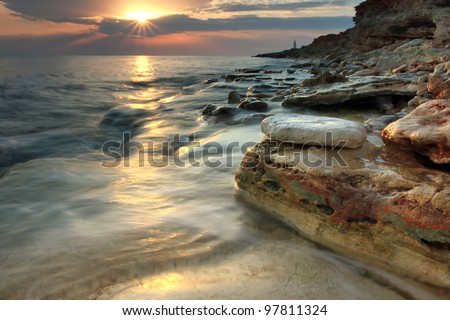 Beautiful rocky sea beach with lighthouse at the sunset