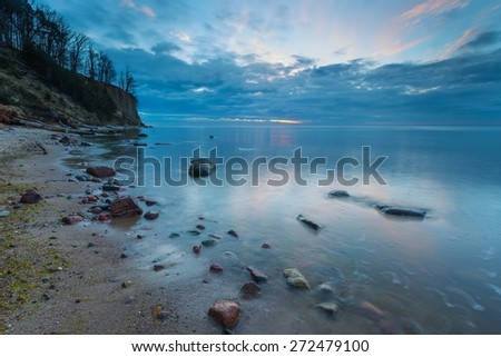 Beautiful rocky sea shore at sunrise or sunset. Long exposure landscape. Baltic sea near Gdynia in Poland. - stock photo
