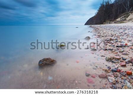 Beautiful rocky sea shore at sunrise or sunset. Long exposure landscape. Baltic sea near Gdynia in Poland. - stock photo
