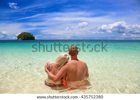 Beautiful romantic couple having fun on the tropical beach sitting with his back to the viewer. Wedding and honeymoon concept. - stock photo