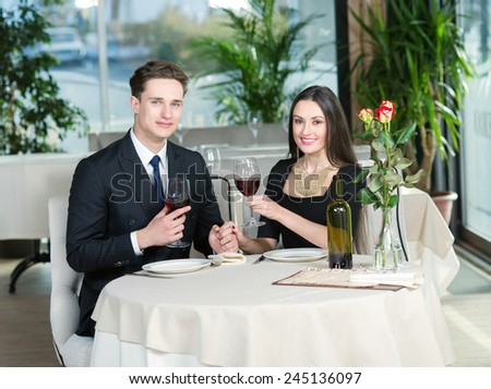Beautiful romantic couple in love is sitting in restaurant together and drinking wine