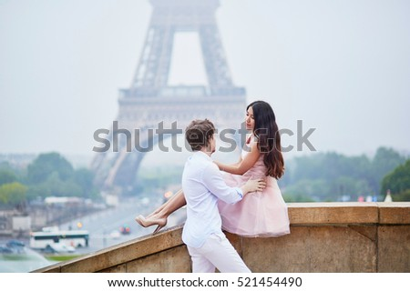Beautiful romantic couple in love near the Eiffel tower on a cloudy and foggy rainy day. Paris, France