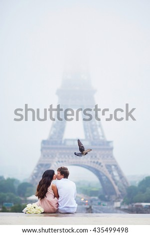 Beautiful romantic couple in love sitting together near the Eiffel tower in Paris on a cloudy and foggy rainy day - stock photo