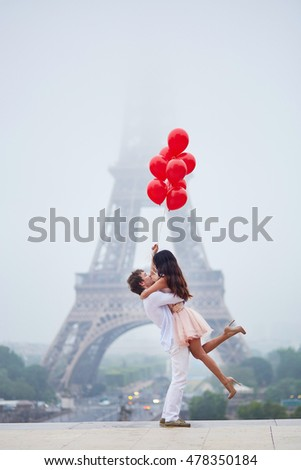 Beautiful romantic couple in love with bunch of red balloons together near the Eiffel tower in Paris on a cloudy and foggy rainy day