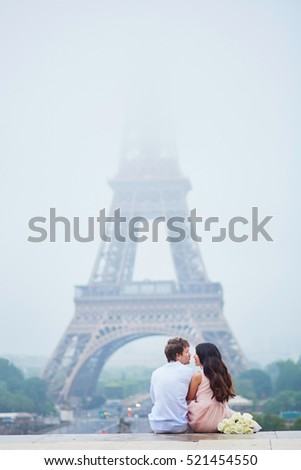 Beautiful romantic couple in love with bunch of white roses sitting near the Eiffel tower on a cloudy and foggy rainy day. Paris, France