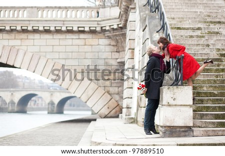 Beautiful romantic couple kissing on a Parisian embankment at spring or winter - stock photo