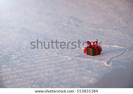 Beautiful romantic gift box on a white snow. Love and St. Valentines Day concept. Winter background.