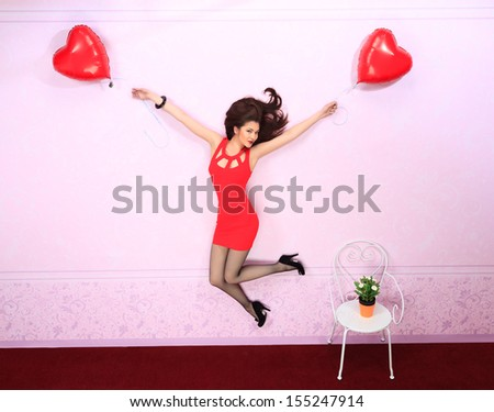 Beautiful romantic girl is flying on a balloons in the shape of heart.
