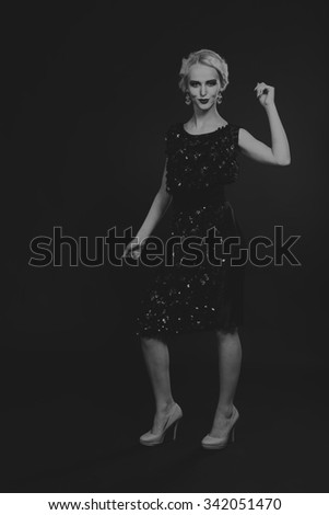 Beautiful romantic image of a girl in 20s style. Beautiful blonde in a stylish dress on a dark background. Professional makeup and jewelry design. Photo for fashion magazines, posters and websites. - stock photo