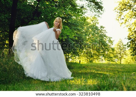 Beautiful romantic stylish blonde bride in white dress dancing in the forest