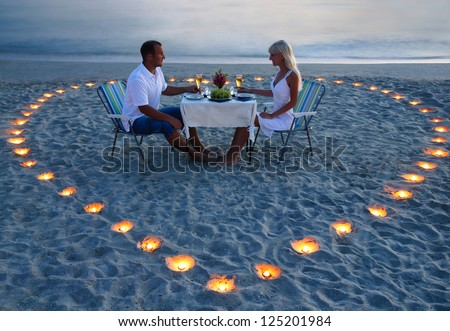 beautiful romantic supper with candles heart on the sand sea beach - a couple of newlyweds or lovers - stock photo