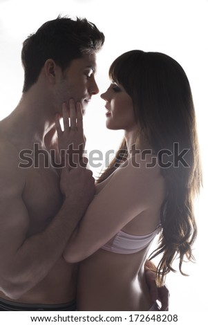 Beautiful romantic young lovers holding each other close as the woman tenderly caresses the mans face as he looks into her eyes, both naked except for her bra, - stock photo