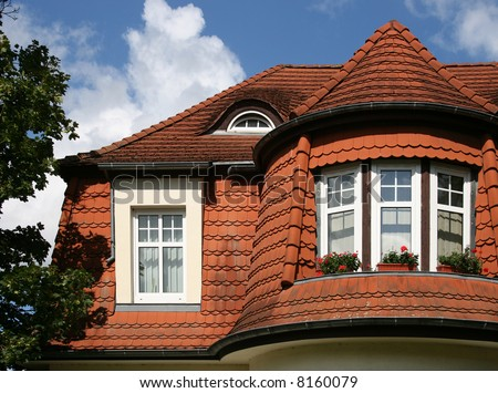 Beautiful roof of a city house with red roofing tiles