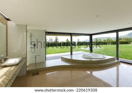 beautiful room with jacuzzi, window overlooking the garden - stock photo