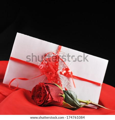 beautiful  rose and letter with ribbon on red close up