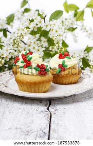 Beautiful rose cupcake and bird cherries in the background - stock photo