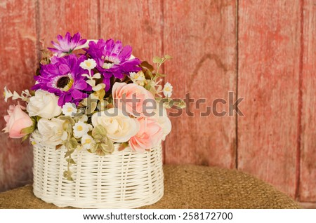 Beautiful roses flowers in a basket,on wooden backgrounds in vintage retro style. - stock photo