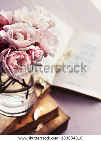 Beautiful Roses in a glass vase with books in vintage style - stock photo