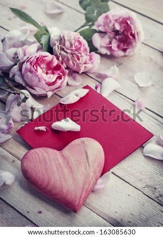 Beautiful roses with old paper card on wooden background/ valentines day romantic background - stock photo