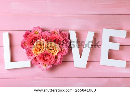 Beautiful roses with word LOVE on pink wooden planks background - stock photo