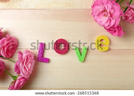 Beautiful roses with word LOVE on wooden background - stock photo