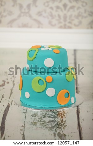 Beautiful round double tier blue green and orange polka dot birthday party cake on vintage wallpaper background and distressed white washed wooden floor