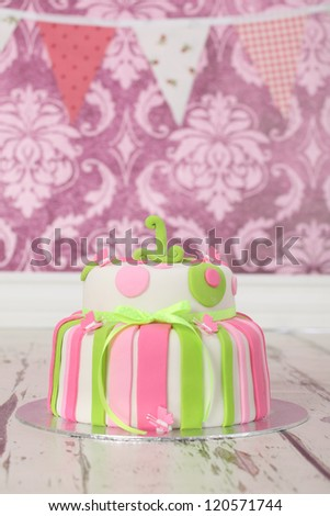 beautiful round double tier polka dot and stripe birthday party cake in white green and pink colours on wooden floor and vintage pink floral wallpaper background - stock photo