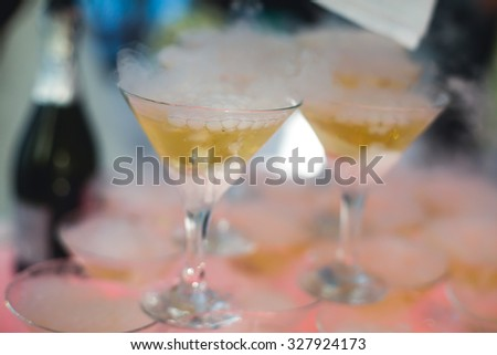 Beautiful row line of different colored alcohol cocktails with mint on a open air party, martini, vodka with bubbles,and others on decorated catering bouquet table on open air event, picture