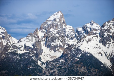 Beautiful rugged rocky Teton snow capped mountain range blue sky majestic landscape scene with dramatic clouds