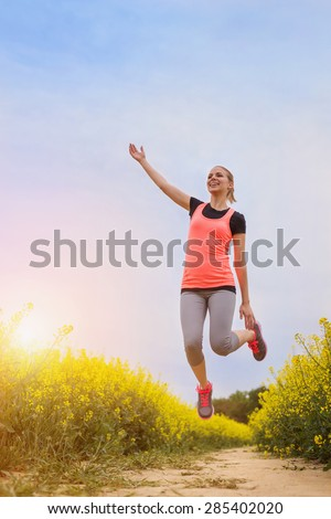 Beautiful runner having fun outside in spring canola field