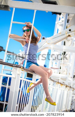 Beautiful russian girl dressed like sailor having fun in summer evening at a big cruise ship