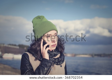 Beautiful Russian girl talking on the phone and gets the bad news. - stock photo