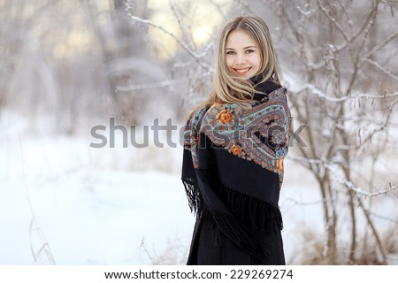 Beautiful Russian woman in a scarf in winter - stock photo